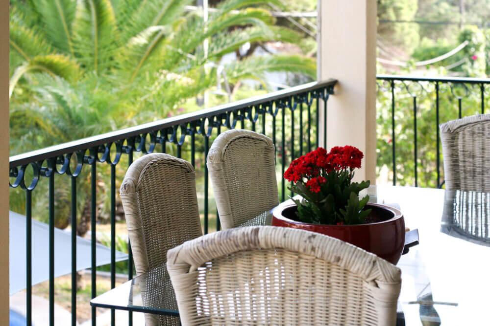 Varanda com mesa para refeições no jardim com piscina